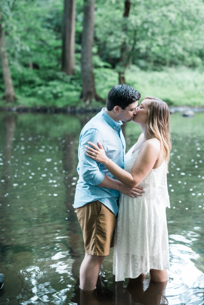 Beautiful couple kissing in river at their engagement session